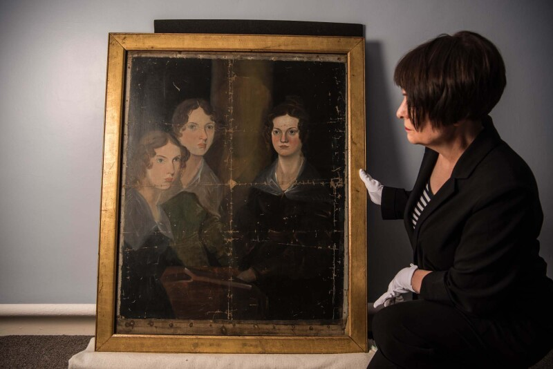 Curator-Ann-Dinsdale-inspects-Bronte-Sisters-portrait-as-it-returns-to-Bronte-Parsonage-Museum.Credit-Guzelian.jpg
